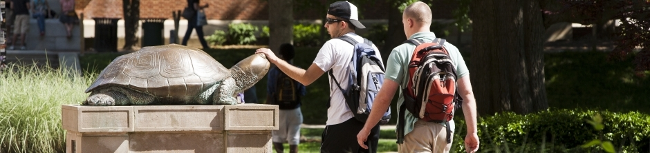 2 Freshman students walk by Testudo, 1 student rubs Testudo's head for luck